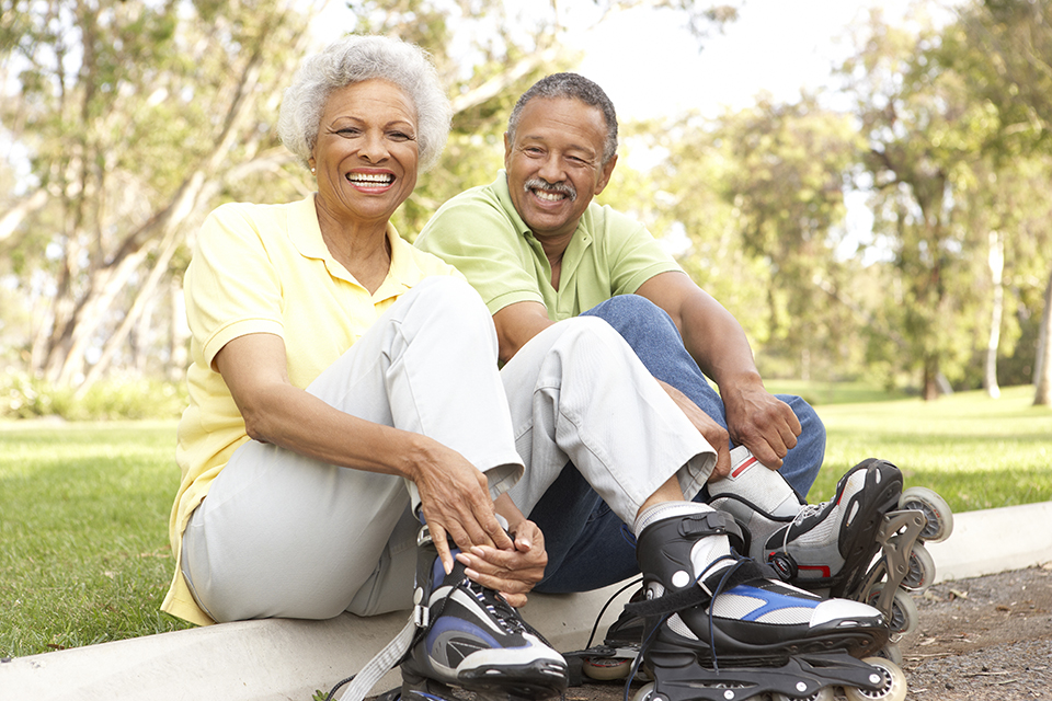An elderly couple rollerblading together.